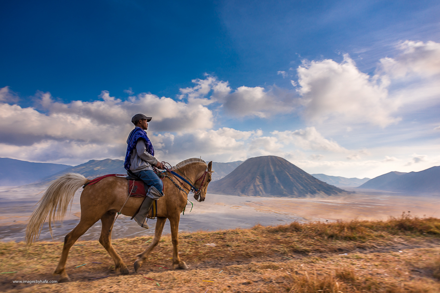 A man ridng a horse with Mount Batok in the background